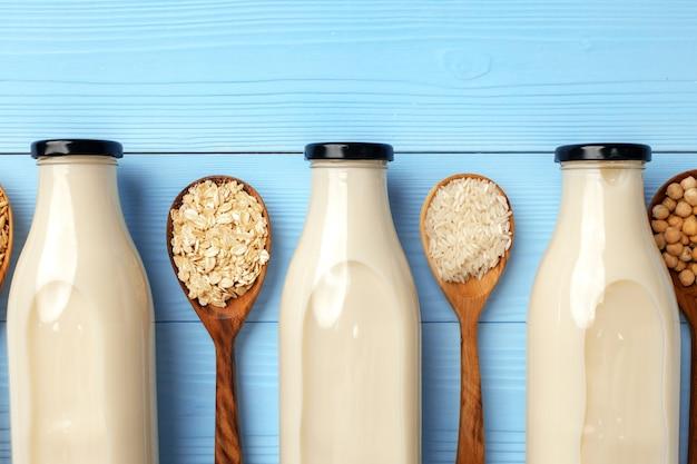 Konzept der veganen bio-nichtmilch mit glasmilchflasche und schüttgütern auf holz