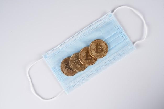 Konzept der verbindung zwischen fall und wachstum der kryptowährung mit goldenen bitcoins des coronavirus isoliert auf weißem hintergrund, nahaufnahme mit kopienraum