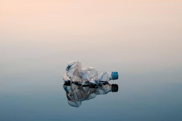 Konzept der verschmutzung, kreativ. eine plastikflasche, die in den ozean schwimmt