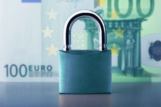 Konzept der versicherung und finanziellen sicherheit. vorhängeschloss gegen euro banknote.