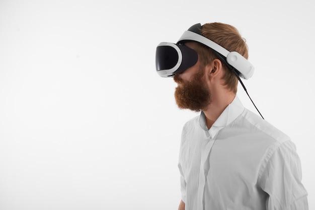 Konzept der visuellen realität und der künstlichen intelligenz. profilaufnahme des bärtigen rothaarigen jungen mannes, der vr headset trägt