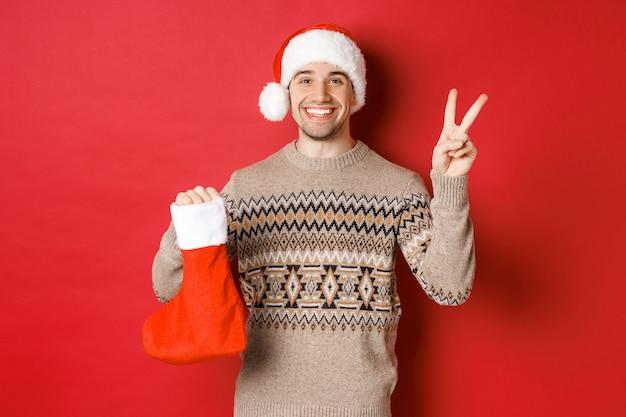 Konzept der winterferien, des neuen jahres und der feier. bild eines glücklich lächelnden mannes in weihnachtsmütze und pullover, der ein friedenszeichen und eine weihnachtsstrumpftasche mit geschenken zeigt, roter hintergrund
