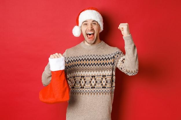 Konzept der winterferien, des neuen jahres und der feier. erstaunter und glücklicher mann, der vor freude schreit, geschenk im weihnachtsstrumpf gefunden und jubelt, die hand hebt und lächelt