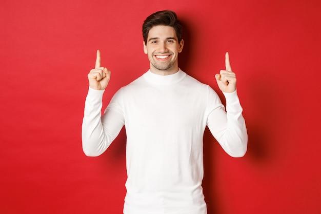 Konzept der winterferien gutaussehender junger mann mit borsten, der weißen pullover trägt, der weihnachten zeigt...