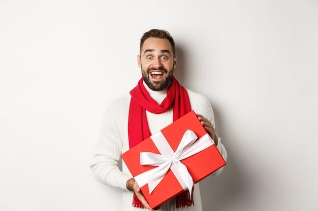 Konzept der winterferien. überraschter mann, der ein weihnachtsgeschenk erhält und erstaunt aussieht, eine rote verpackte schachtel mit geschenk hält und auf weißem hintergrund steht