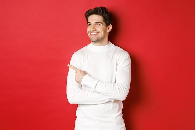 Konzept der winterferien weihnachten und lifestyle schöner erwachsener mann im weißen pullover suchen und p...