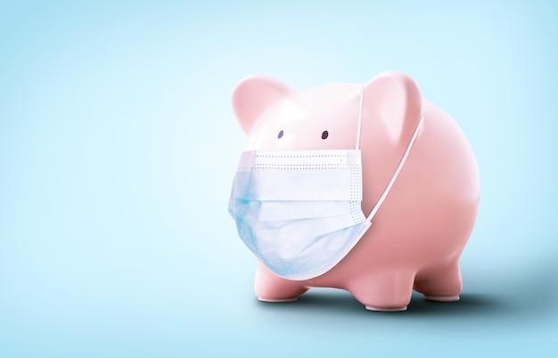 Konzept der wirtschaftskrise. kreatives schwein mit medizinischer maske. geld und pillen. coronavirus (covid-19)-pandemie und der zusammenbruch der wirtschaft