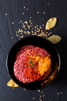 Konzept der zutaten für die lebensmittelzubereitung bio-rohhackfleisch oder rinderhackfleisch, mariniert mit gewürzen für orientalisches essen keema-curry auf schwarzem schieferstein mit kopierraum