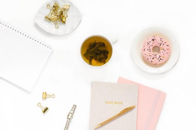 Konzept des arbeitsplatzes einer frau eines freiberuflers oder bloggers. notizbücher, ein stift, ein rosa donut auf einem weißen teller, eine tasse grüner tee auf einer weißen oberfläche morgen, frühstück zu hause am arbeitsplatz