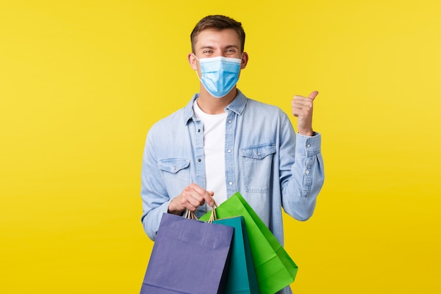 Konzept des ausbruchs der covid-19-pandemie, des einkaufs und des lebensstils während des coronavirus. fröhlicher, gutaussehender blonder mann in medizinischer maske, der sich über geöffnete einkaufszentren freut, daumen hoch zeigt und taschen trägt.