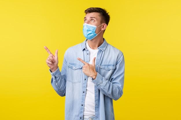 Konzept des ausbruchs der covid-19-pandemie, lebensstil während der sozialen distanzierung des coronavirus. neugieriger gutaussehender mann in medizinischer maske, drehen sie das gesicht in die obere linke ecke und lesen sie das schild auf gelbem hintergrund.