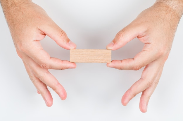 Konzept des auserlesenen mannes, der holzetikett mit beiden händen hält. auf weißem hintergrund draufsicht. horizontales bild