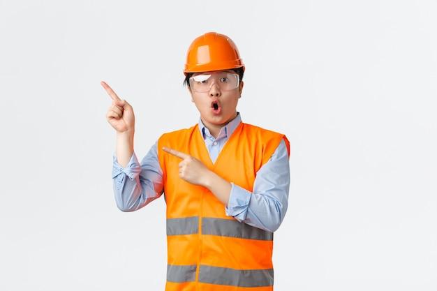 Konzept des bausektors und der industriearbeiter. überraschter und beeindruckter asiatischer männlicher ingenieur, bauleiter in der fabrik mit schutzhelm, reflektierender kleidung und zeigender oberer linker ecke.