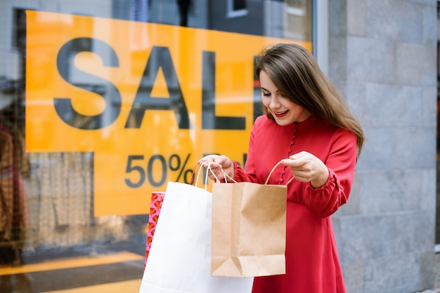 Konzept des black friday sales. glückliches kaukasisches mädchen, das nahe fenster eines einkaufszentrums mit inschrift verkauf steht, durch einkäufe schaut, die sie tat und gefühl der belustigung und freude ausdrückt