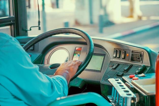 Konzept des busfahrerlenkrads und des fahrgastbusses. hände des fahrers in einem modernen bus durch fahren