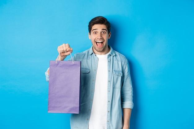 Konzept des einkaufens, des urlaubs und des lebensstils. aufgeregter gutaussehender kerl, der papiertüte mit geschenk hält und glücklich aussieht und auf blauem hintergrund steht