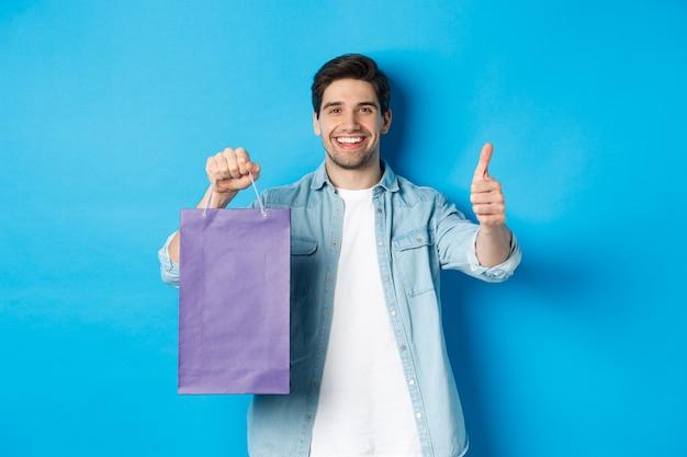 Konzept des einkaufens, des urlaubs und des lebensstils. zufriedener lächelnder mann, der papiertüte hält, daumen hoch zeigt und geschäft empfiehlt, stehend über blauem hintergrund.
