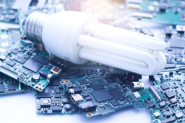 Konzept des elektronischen abfalls, alte kompaktleuchtstofflampe auf leiterplatte.
