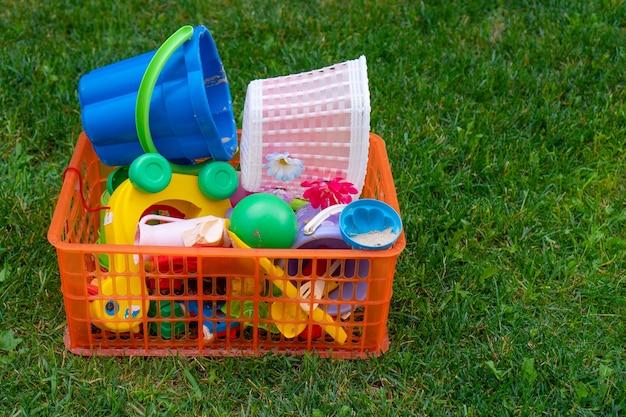 Konzept des entwicklungsspiels für kinder. kinderspielzeug auf der grünen wiese, kinderspielzeugkiste auf grünem gras. selektiver fokus.