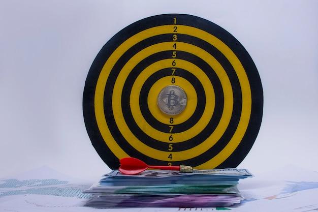 Konzept des erfolgs und der zielerreichung. runde dartscheibe mit einem bündel dollar, euro und einer bitcoin-münze in der mitte des kreises vor dem hintergrund von grafiken und diagrammen auf papier.