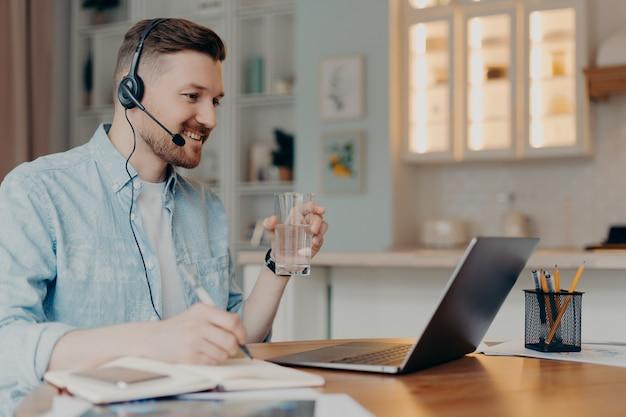 Konzept des fernstudiums. millennial guy student in headset watch webinar hat online-unterricht während der quarantäne genießt internet-bildung trinkt wasser aus glas macht notizen posen auf dem desktop