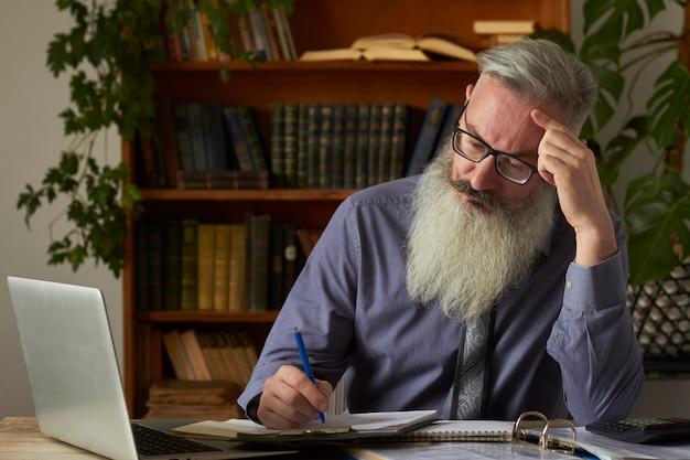 Konzept des fernunterrichts. lehrer tutor schaut auf laptop und macht notizen in einem notizbuch