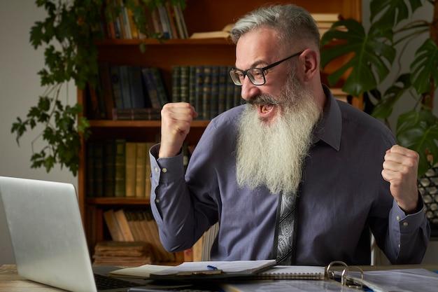 Konzept des fernunterrichts. lehrer tutor schaut auf laptop und zeigt siegesgeste