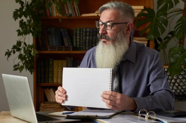 Konzept des fernunterrichts. lehrer, übersetzer, tutor am desktop in der bibliothek zeigt eine leere platte auf dem laptop-bildschirm