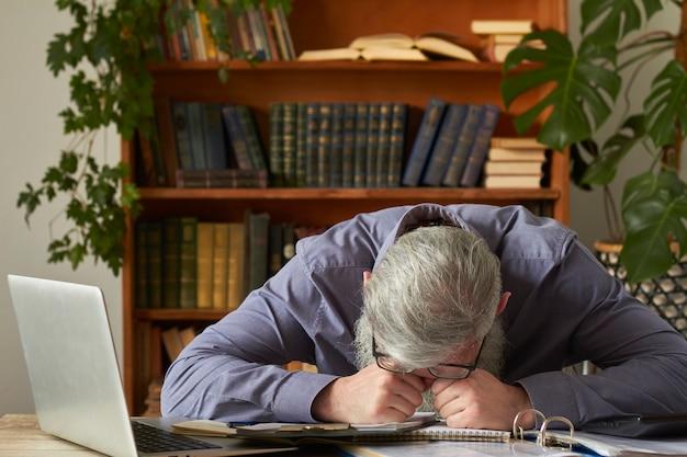 Konzept des fernunterrichts. müde verärgerte lehrer tutor legte seinen kopf auf die fäuste