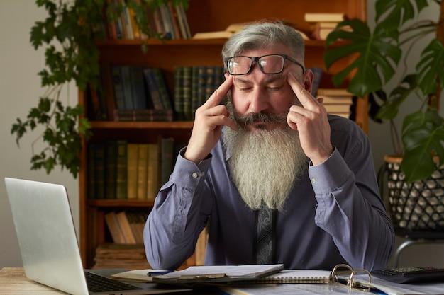 Konzept des fernunterrichts. müde verärgerte lehrer tutor schaut auf laptop und massiert die schläfen