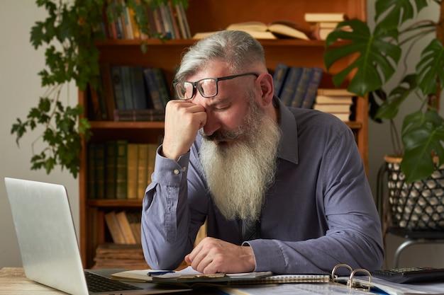 Konzept des fernunterrichts. müder verärgerter lehrer tutor, der auf laptop schaut und seinen kopf umklammert