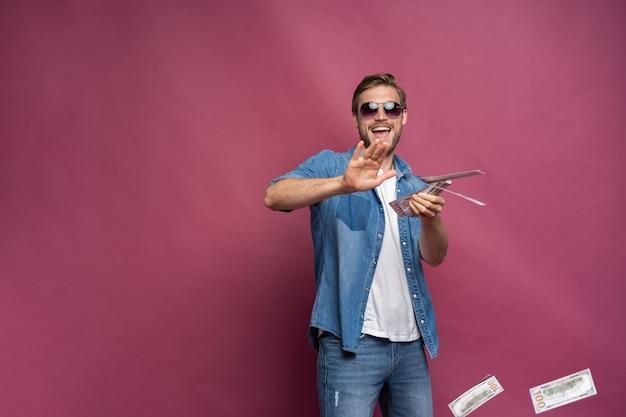 Konzept des finanziellen reichtums, des wohlstands und der lotteriegewinne - mann, der sein geld einzeln auf rosafarbenem hintergrund wegwirft