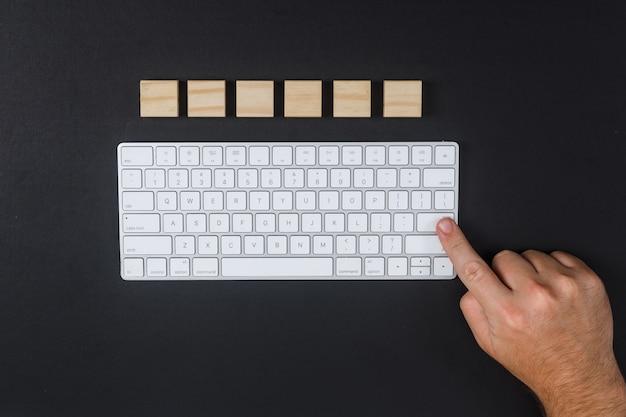 Konzept des forschungsmannes, der die eingabetaste drückt. mit tastatur, holzwürfel auf schwarzem schreibtischhintergrund flach liegen. horizontales bild