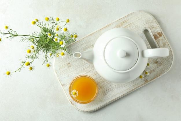 Konzept des frühstücks mit kamillentee auf weißem strukturiertem tisch