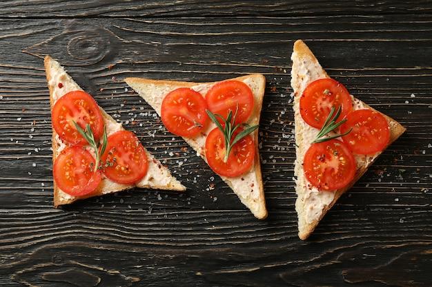 Konzept des frühstücks mit toast mit tomate auf hölzernem hintergrund