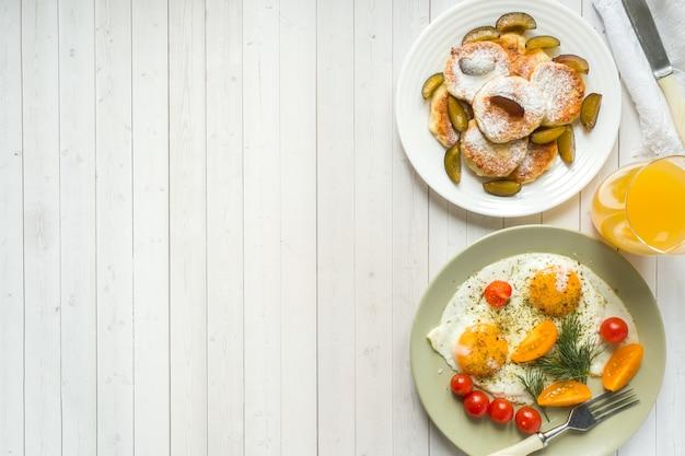 Konzept des frühstücks. spiegeleier, hüttenkäsepfannkuchen, pflaumen und haferflocken mit milch, orangensaft auf dem tisch