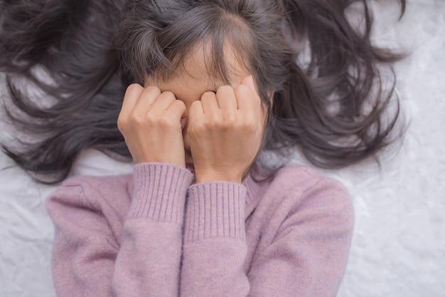Konzept des gebrochenen herzens. frau schläft und schließt die augen mit ihr auf dem bett. sie weint und bedauert.
