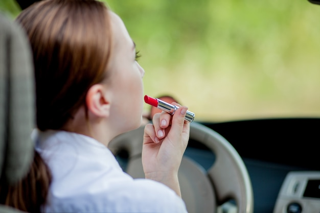 Konzept des gefahrenfahrens. rothaariges junges mädchen des fahrers der jungen frau, die ihre lippen malt, die das schminken beim fahren des autos tun