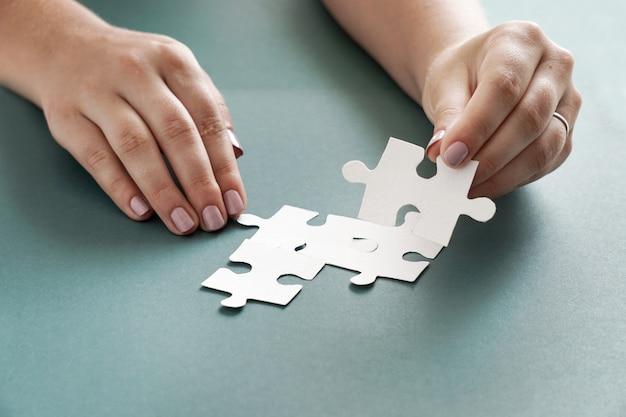 Konzept des geschäfts, frauenhände, die weiße puzzleteile auf dem blauen hintergrund halten