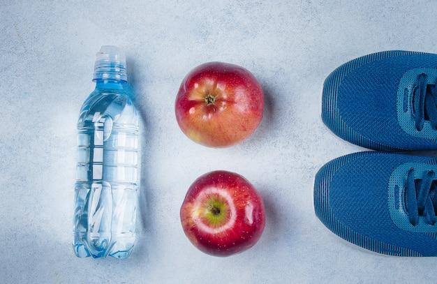 Konzept des gesunden lebensstils. flache lage der blauen turnschuhe, des apfels und der wasserflasche auf bluebackground.
