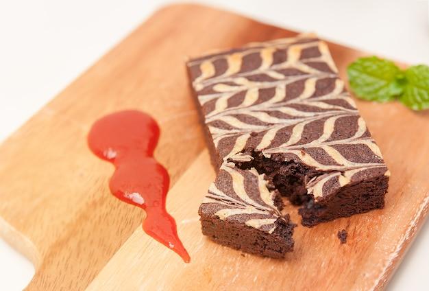 Konzept des gesunden nachtischs, fettarmer brownie auf hölzerner platte mit erdbeersoße