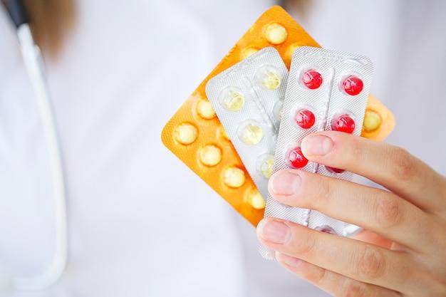 Konzept des globalen gesundheitswesens und der medizin. doktor holding pack der unterschiedlichen tablet-blasen-nahaufnahme. lebensrettungsdienst, legale drogerie, verschreibungspflichtige medikamente, blutdruck