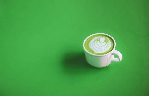 Konzept des grünen tees, milch des grünen tees mit kunst auf die oberseite mit weißer schale auf grünem hintergrund