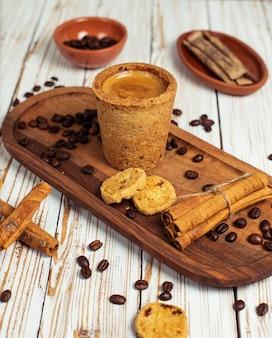 Konzept des gutenmorgens - schaumiger espressokaffee des frühstücks begleitet von den köstlichen plätzchen und vom zimt