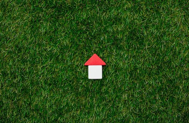 Konzept des hölzernen spielzeughauses auf grünem gras.