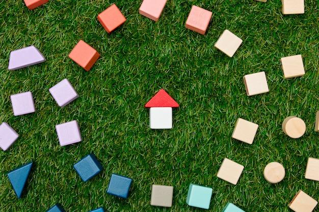 Konzept des hölzernen spielzeughauses und anderer blöcke herum auf grünem gras.