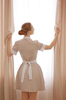Konzept des hotelservice. zimmermädchen passt gardinen im zimmer an