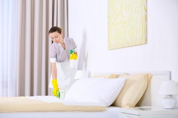 Konzept des hotelservice. zimmermädchen säubert nachttisch von staub