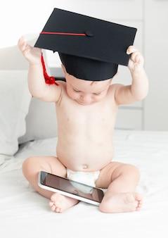 Konzept des intelligenten babys. netter kleiner junge in abschlusskappe, der auf digitalem tablet im internet surft