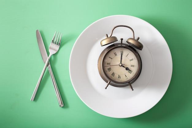 Konzept des intermittierenden fastens, der ketogenen ernährung, des gewichtsverlusts. gabel und messer gekreuzt und wecker auf teller